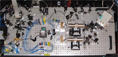 Optical assembly of  FIRST-18, on a 1m20 by 60 cm platform;  the optical fibres are shown in blue, and the scientific camera is on the right.